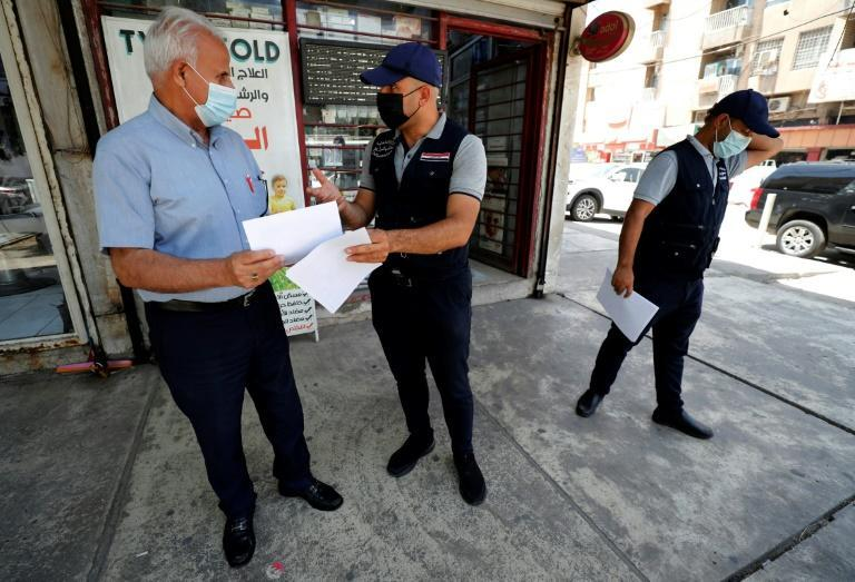 """Members of the Iraqi Interior Ministry's anti-""""fake news"""" team hand out leaflets on identifying misinformation in the capital Baghdad"""