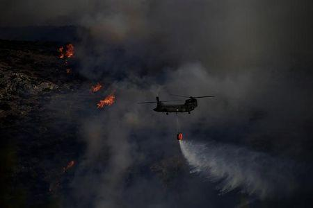 A Chinook helicopter makes a water drop as a wildfire burns in the area of Kalyvia, near Athens, Greece July 31, 2017. REUTERS/Alkis Konstantinidis