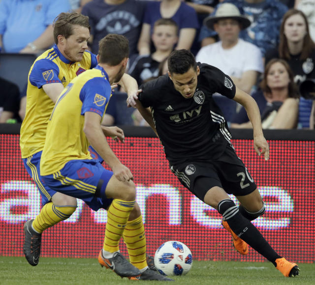Sporting Kansas City forward Daniel Salloi (20) gets around Colorado Rapids defenders on a goal-scoring play during the first half of an MLS soccer match in Kansas City, Kan., Saturday, May 5, 2018. (AP Photo/Orlin Wagner)