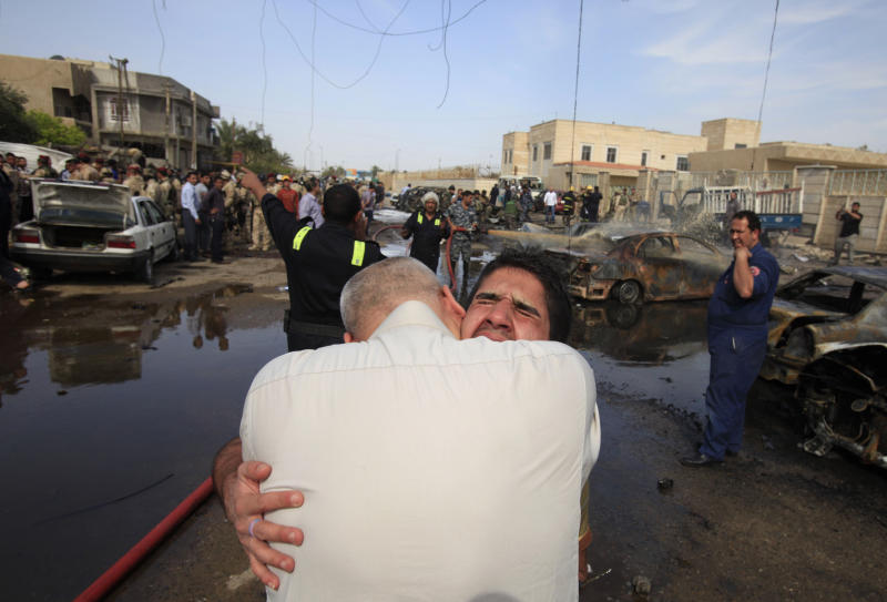 An Iraqi man is comforted at the scene of a car bomb attack in Baghdad, Iraq, Friday, March 29, 2013. A parked car bomb exploded near the al-Mahdi mosque in the northeastern Binook neighborhood as worshippers were leaving Friday prayers, killing and wounding several, just one of a string of bombings targeting Shiite mosques on Friday, killing and wounding dozens of people, police said.(AP Photo/Karim Kadim)