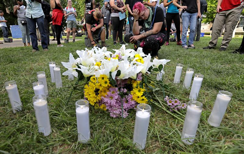 """People pay their respects at a vigil where 20 candles were burned for the 19 people injured and one killed when a car plowed into a crowd of counter-protesters at the """"Unite the Right"""" rally organized by white nationalists in Charlottesville, Virginia. (Jim Bourg / Reuters)"""