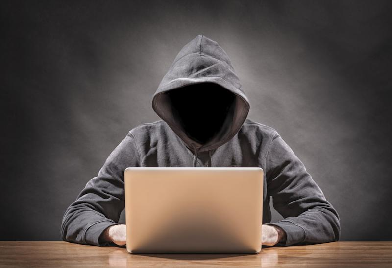 man wearing hoodie with his face in shadow using a laptop