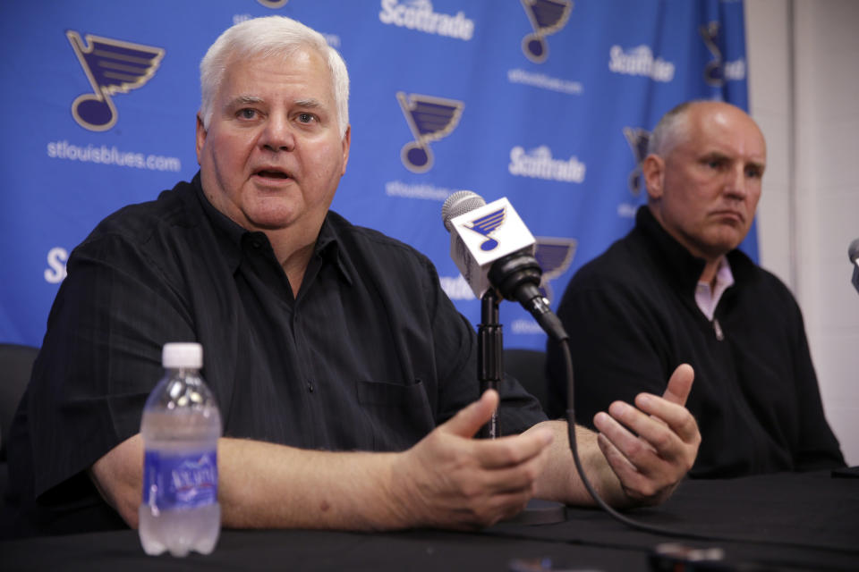 St. Louis Blues head coach Ken Hitchcock speaks along side general manager Doug Armstrong, right, during a news conference Tuesday, May 26, 2015, in St. Louis. The Blues are sticking with Hitchcock for another season, announcing the veteran NHL hockey coach has signed a one-year contract with the team. (AP Photo/Jeff Roberson)
