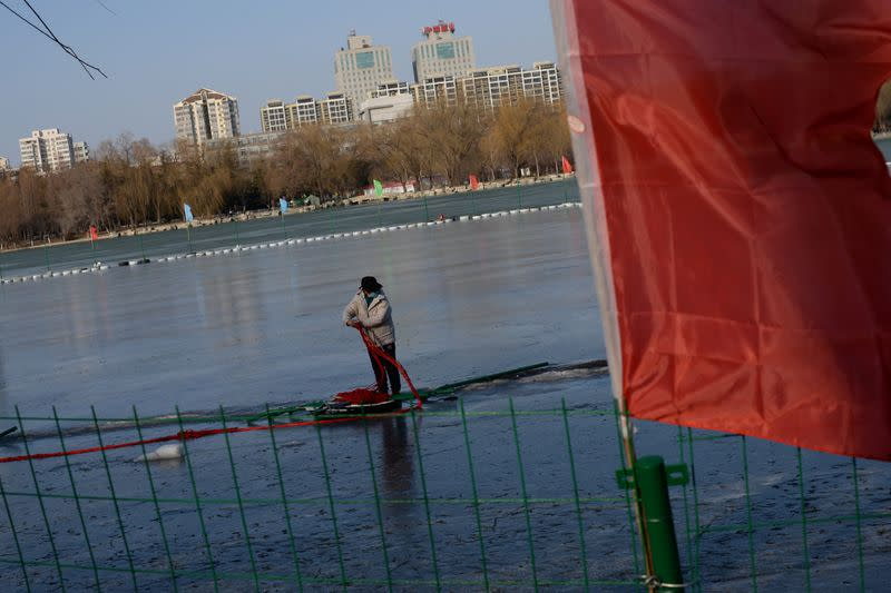 Worker dismantles a closed ice rink on a frozen lake at the Yuyuantan Park, as the country is hit by an outbreak of the new coronavirus, in Beijing