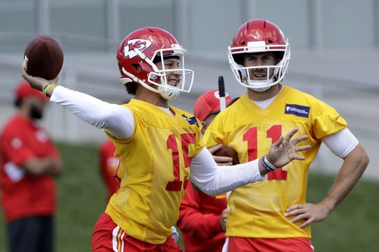 Patrick Mahomes (15) throws as Alex Smith looks on. (AP)