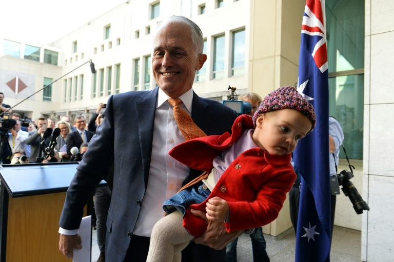 Outgoing Australian Prime Minister Malcolm Turnbull leaves a press conference with his granddaughter Alice after giving his final press in Canberra on Friday