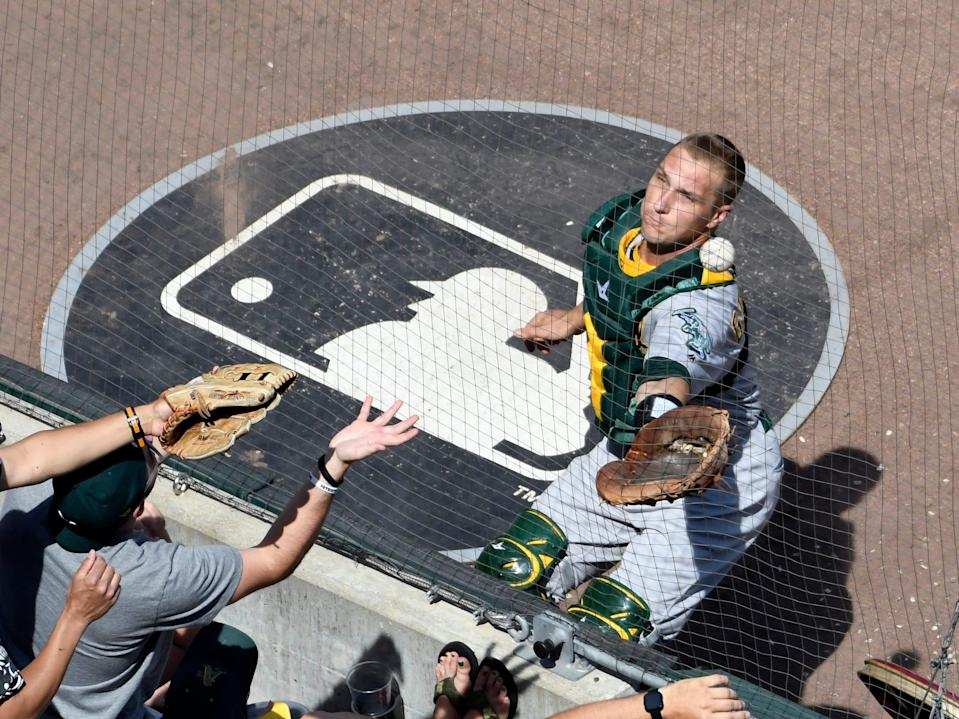 Oakland Athletics catcher Dustin Garneau, right, cannot make a catch on a hit by Chicago White Sox's Ryan Cordell during the third inning of a baseball game, Friday, Aug. 9, 2019, in Chicago. (AP Photo/David Banks)
