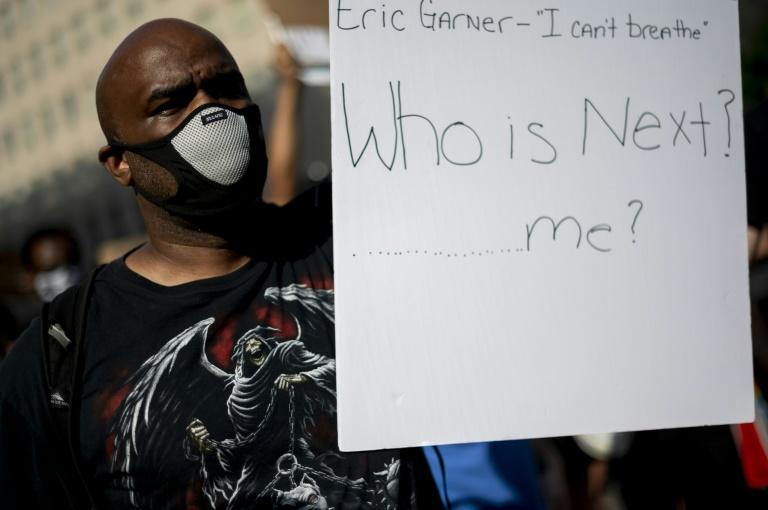 A protestor holds a sign near the White House in Washington, DC, on June 2, 2020. Experts have also warned that racialized violence by police against African Americans is itself a serious health hazard