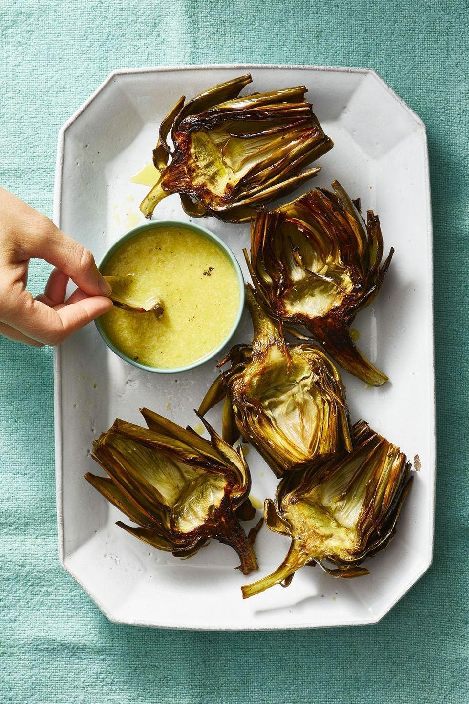 """<p>Artichokes might not be a traditional tailgate food, but that doesn't mean this roasted recipe won't fly off your table just as quickly as the chips do. </p><p><em><a href=""""https://www.goodhousekeeping.com/food-recipes/easy/a19865653/roasted-artichokes-with-caesar-dip-recipe/"""" rel=""""nofollow noopener"""" target=""""_blank"""" data-ylk=""""slk:Get the recipe for Roasted Artichokes with Caesar Dip »"""" class=""""link rapid-noclick-resp"""">Get the recipe for Roasted Artichokes with Caesar Dip »</a></em></p>"""