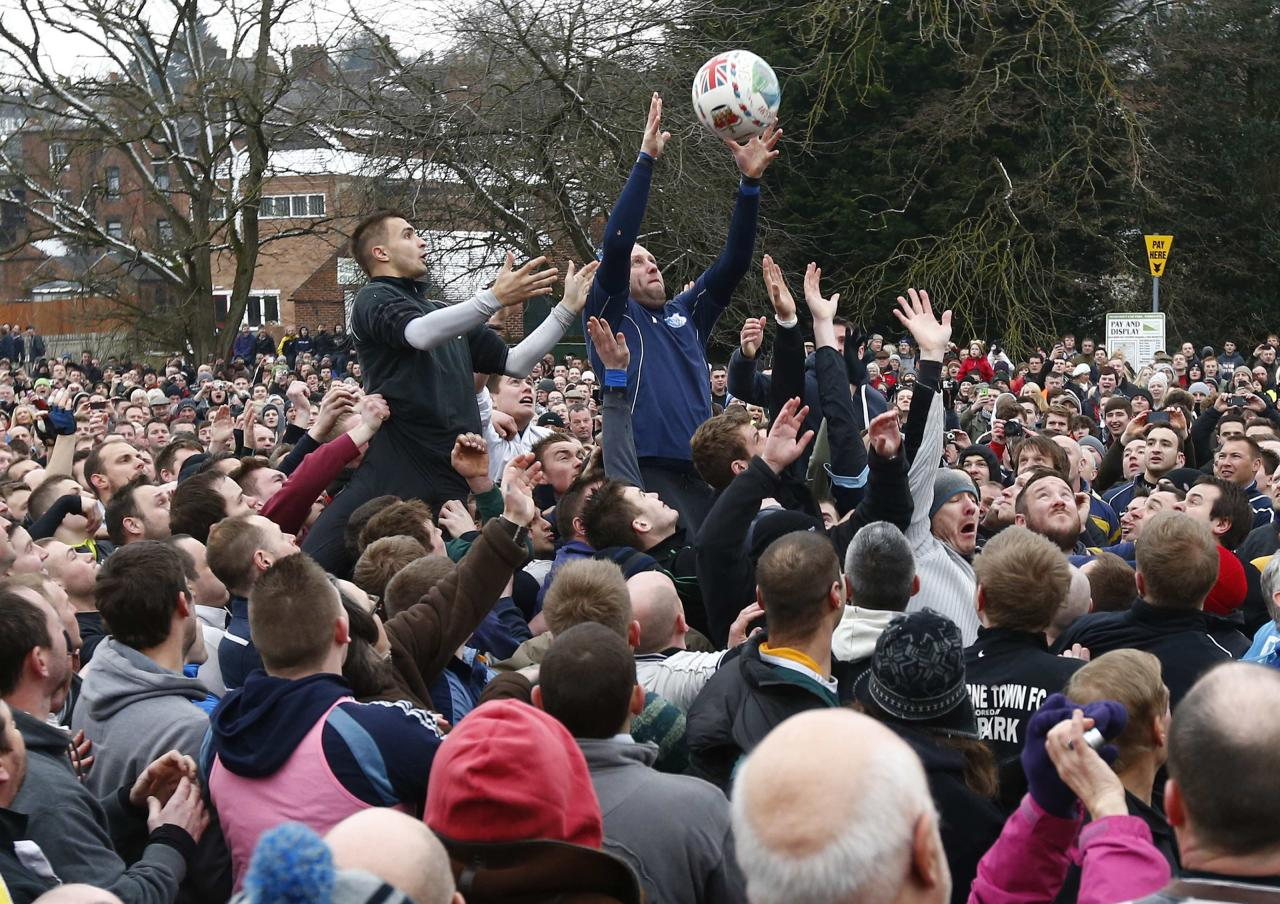 <p>The ball is thrown into the hug to start the annual Shrovetide football match (Reuters)</p>