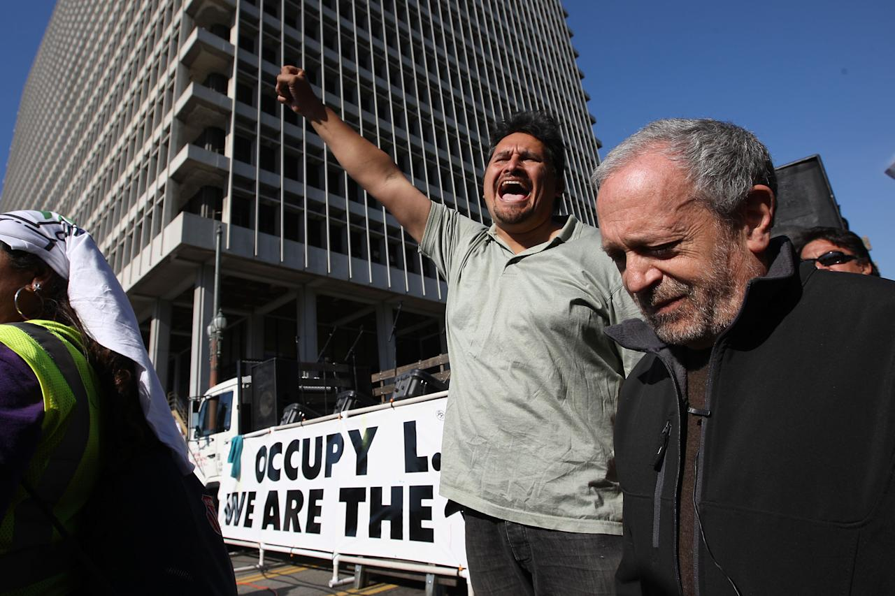 LOS ANGELES, CA - NOVEMBER 5:  Former U.S. Secretary of Labor Robert Reich (R) is cheered as he is introduced to speak to Occupy Los Angeles protesters after the Move Your Money March through the downtown financial district during what is being called Bank Transfer Day, on November 5, 2011 in Los Angeles, California. Occupy movement members are calling for people to move their money from banks to credit unions today in support of the 99% movement.   (Photo by David McNew/Getty Images)