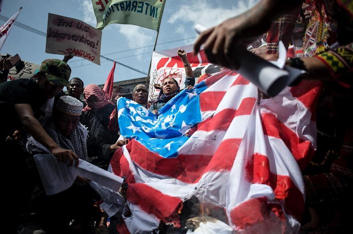Members of an indigenous group and activists burn a US flag during a protest calling for the immediate pull-out of US troops in the Philippines in Manila on October 21, 2016 (AFP Photo/Noel Celis)