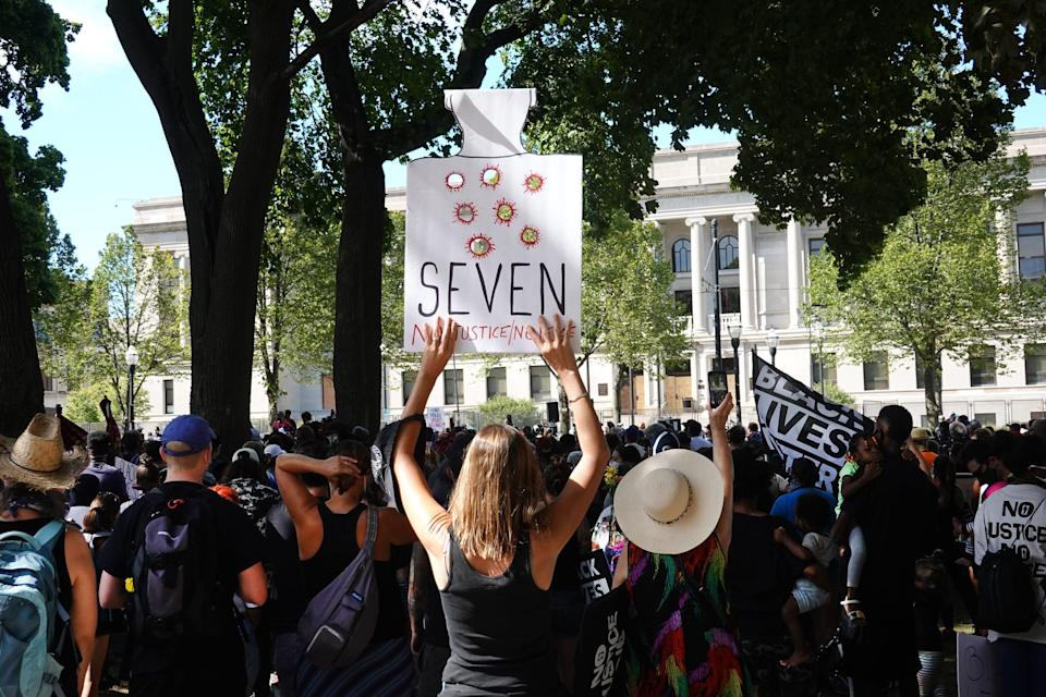 a woman holds a sign with bullet holes in it and the word seven at a rally supporting jacob blake