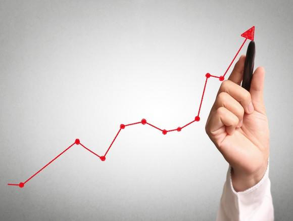 A hand drawing a rising stock chart.