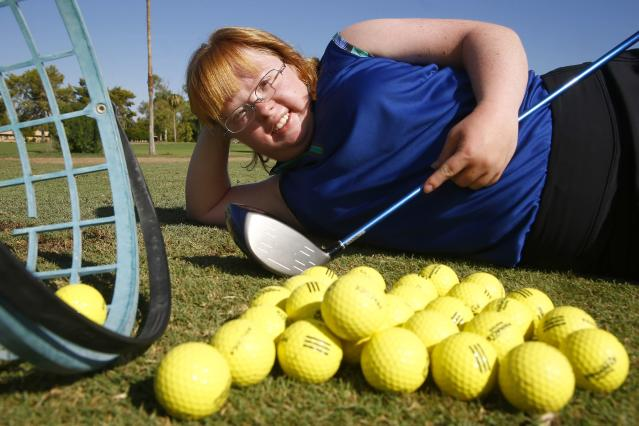 In this Aug. 28, 2019, photo, Amy Bockerstette, the Down syndrome golfer who was an internet sensation by making par at the 16th hole at the Phoenix Open with soon-to-be 2019 U.S. Open champion Gary Woodland, poses for a photograph after practicing with her teaching pro at Palmbrook Country Club in Sun City, Ariz. (AP Photo/Ross D. Franklin)