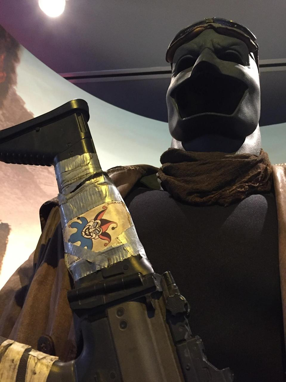 <p>This is a closeup of the outfit the Dark Knight was wearing in his vision of alien invaders; note the playing card on his machine gun.</p>