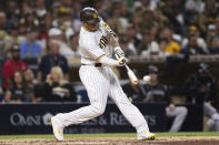 San Diego Padres' Manny Machado hits an RBI single during the seventh inning of the team's baseball game against the Colorado Rockies, Friday, July 9, 2021, in San Diego. AP Photo/Derrick Tuskan)
