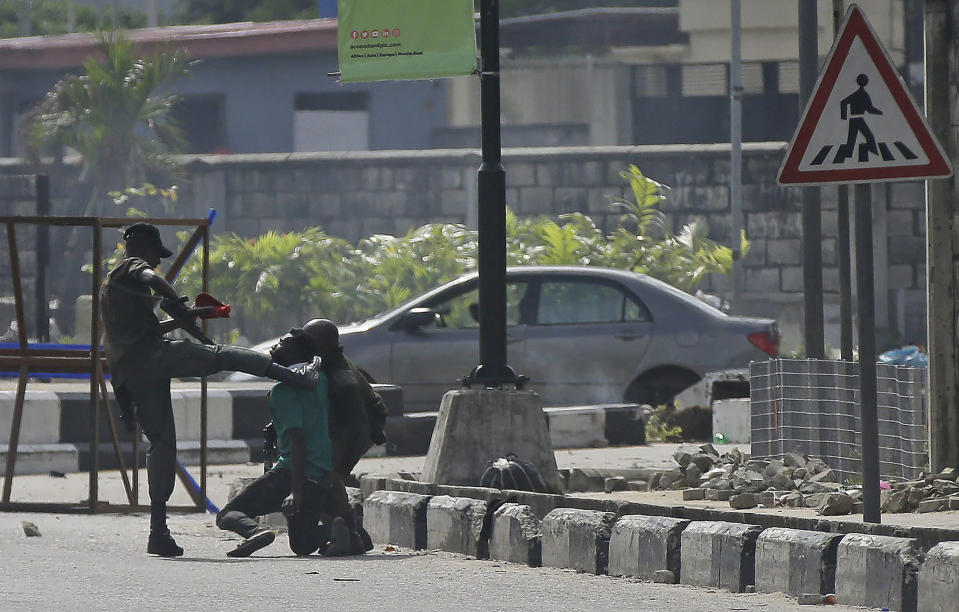 Police officers detain a protester at the Lekki toll gate in Lagos, Nigeria, Wednesday Oct. 21, 2020. After 13 days of protests against alleged police brutality, authorities have imposed a 24-hour curfew in Lagos, Nigeria's largest city, as moves are made to stop growing violence.( AP Photo/Sunday Alamba)