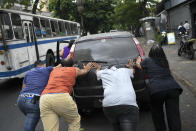 """FILE - In this May 25, 2020 file photo, people push a car that ran out of gas to a state-run oil company PDVSA filling station during a fuel crunch in Caracas, Venezuela. With motorists waiting in lines to fill up their cars with gas that is increasingly scarce, the government proposed in Oct. 2020 to the Constitutional Assembly an """"Anti-Blockade Law,"""" to get around U.S. sanctions. (AP Photo/Matias Delacroix, File)"""
