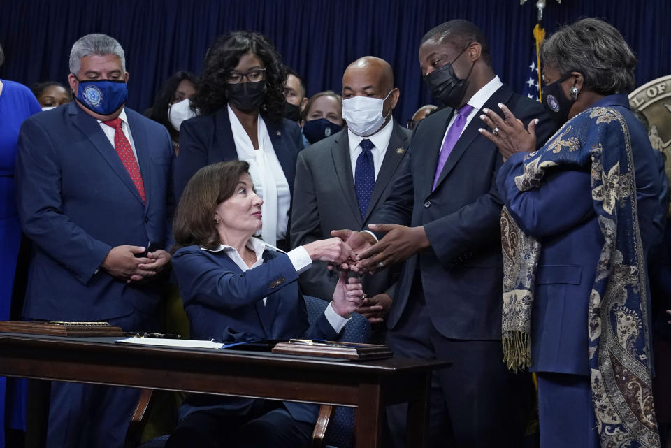 """New York Gov. Kathy Hochul, seated, hands the first pen, during the signing of the """"Less is More"""" law, to Lt. Gov. Brian Benjamin during ceremonies in the governor's office, in New York, Friday, Sept. 17, 2021. New Yorkers will be able to avoid jail time for most nonviolent parole violations under a new law that will take effect in March 2022, and largely eliminates New York's practice of incarcerating people for technical parole violations. (AP Photo/Richard Drew)"""