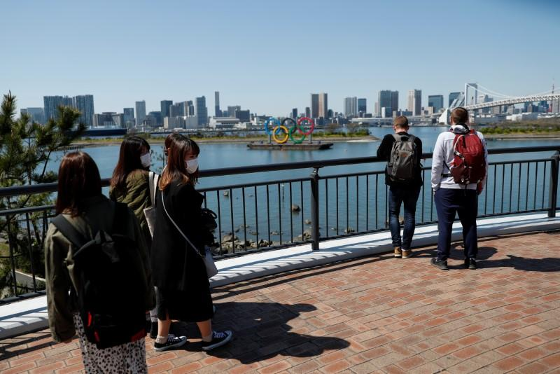 People wearing protective face masks due to the outbreak of coronavirus disease (COVID-19) walk and look in front of the Giant Olympic rings at the waterfront area at Odaiba Marine Park in Tokyo