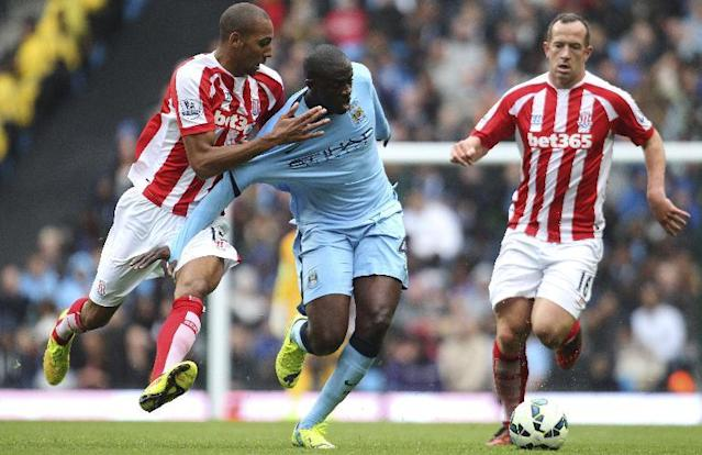 Stoke City's Steven N'Zonzi, left, and Charlie Adam, right, tackle Manchester City's Yaya Toure during their English Premier League soccer match at the Etihad Stadium, Manchester, England, Saturday Aug. 30, 2014. (AP Photo/Lynne Cameron, PA)