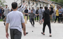 Players celebrate after taking a wicket as migrants play a game of cricket in Blazuj migrant camp in Bosnia's capital of Sarajevo Wednesday, May 19, 2021. (AP Photo/Kemal Softic)