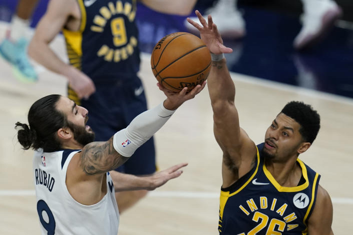 Minnesota Timberwolves' Ricky Rubio (9) has his shot blocked by Indiana Pacers' Jeremy Lamb (26) during the first half of an NBA basketball game, Wednesday, April 7, 2021, in Indianapolis. (AP Photo/Darron Cummings)