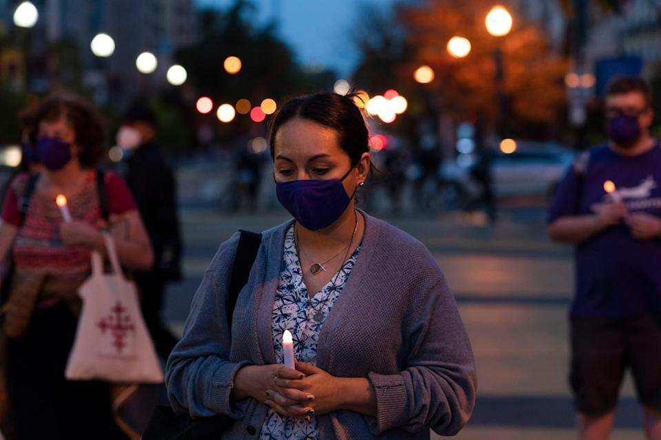 """Norma Cindy Canedo holds a candle during the """"Mourning Into Unity"""" vigil on Monday night on the section of 16th Street that has been renamed Black Lives Matter Plaza near the White House."""
