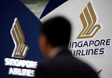 FILE PHOTO - A man walks past a Singapore Airlines signage at Changi Airport in Singapore May 11, 2016. REUTERS/Edgar Su/File Photo