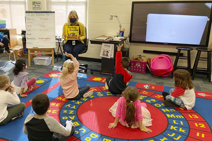 """In this photo provided by Julie Mackett, the kindergarten teacher conducts her class at Ft. Meigs Elementary School, in Perrysburg, Ohio. Contact tracing and isolation protocols meant to contain the spread of the coronavirus are sidelining school employees and frustrating efforts to continue in-person learning. """"I think everybody understands when you can't have enough subs to fill the roles, it's also a safety issue: You can't have that many children without support from adults,"""" said Mackett, who went through her own two-week quarantine early in the school year after a student tested positive. (Courtesy of Julie Mackett via AP)"""
