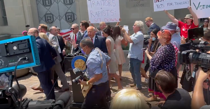 Reps Marjorie Taylor Greene, Matt Gaetz, Louie Gohmert and others are ushered away by security as protesters crowded and shouted down the group during a press conference outside of the Justice Department (Twitter: Zachary Petrizzo)