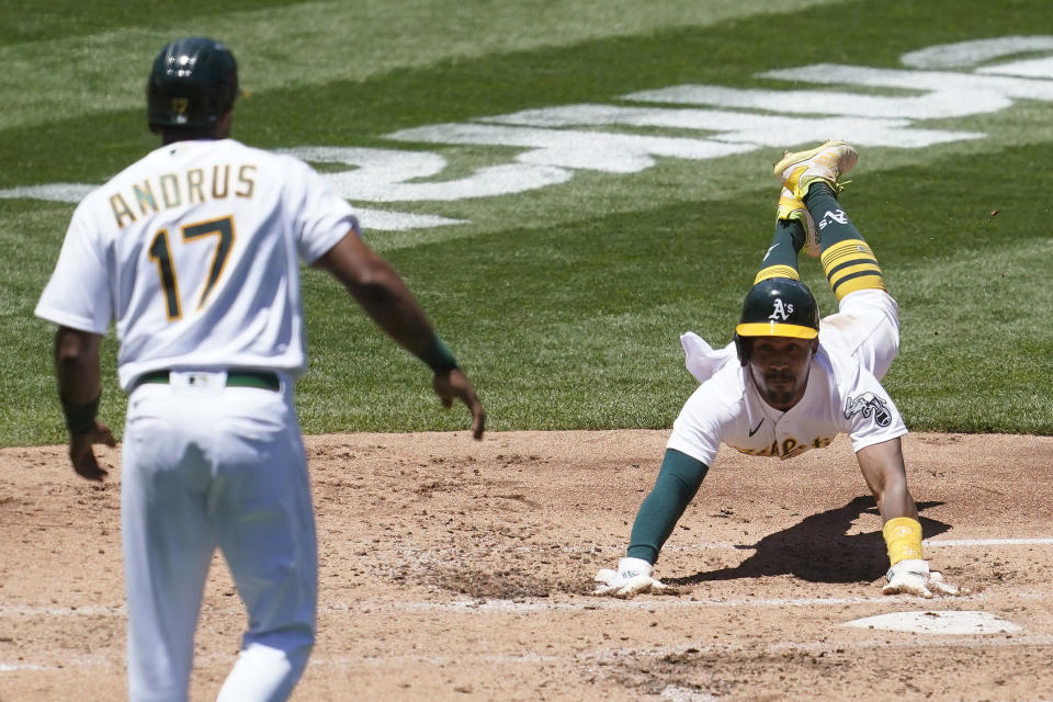 Oakland Athletics' Elvis Andrus (17) watches as Tony Kemp slides home as both scored on a two-run double hit by Matt Chapman during the second inning of a baseball game against the Kansas City Royals in Oakland, Calif., Saturday, June 12, 2021. (AP Photo/Jeff Chiu)