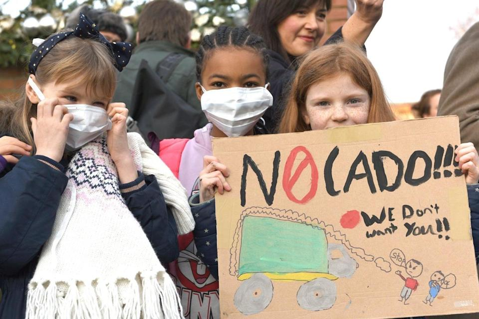 Concerned: children wear face masks and wave placards in protest