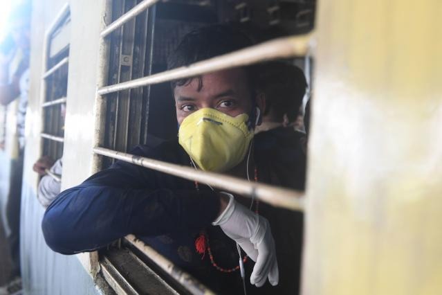 A passenger wearing a facemask travels in a train during a one-day Janata (civil) curfew imposed as a preventive measure against the COVID-19 coronavirus, at a railway station in Kolkata on March 22, 2020. - Nearly one billion people around the world were confined to their homes, as the coronavirus death toll crossed 13,000 and factories were shut in worst-hit Italy after another single-day fatalities record. (Photo by Dibyangshu SARKAR / AFP) (Photo by DIBYANGSHU SARKAR/AFP via Getty Images)
