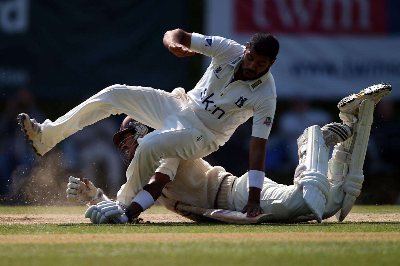 LONDON, ENGLAND - JUNE 07:  Arun Harinath of Surrey collides head first with Jeetan Patel of Warwickshire during day three of the LV County Championship Division One match between Surrey and Warwickshire at Guildford Cricket Club on June 07, 2013 in Guildford, England.  (Photo by Clive Rose/Getty Images)
