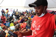Selomourd Menrrivil, from Cap-Haitien, Haiti, looks at his cell phone as he gathers with other migrants in Monterrey, Mexico, Thursday, Sept. 23, 2021. Menrrivil, 43, continued receiving daily updates all week from other Haitians in Del Rio and Ciudad Acuña, after arriving with his wife and two teen daughters, and has decided to legalize his status in Mexico. (AP Photo/Marcos Martinez Chacon)