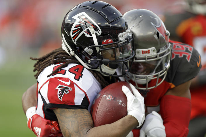 Atlanta Falcons running back Devonta Freeman (24) is stopped by Tampa Bay Buccaneers strong safety Andrew Adams (39) on a run during the first half of an NFL football game Sunday, Dec. 29, 2019, in Tampa, Fla. (AP Photo/Chris O'Meara)