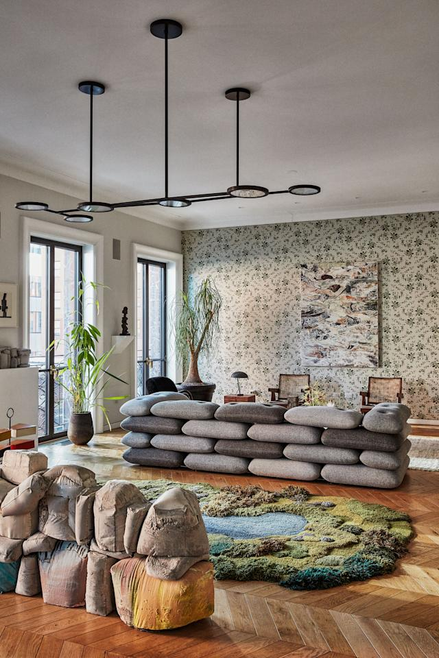 Andrew Zuckerman and Niki Bergen's Manhattan loft is furnished with an Alexandra Kehayoglou rug, brick sofa by Kibisi, Matter Made light fixture, and sculpture (foreground) and painting by Christopher Astley; the Cannonball wallpaper is from the couple's new line, Superflower.