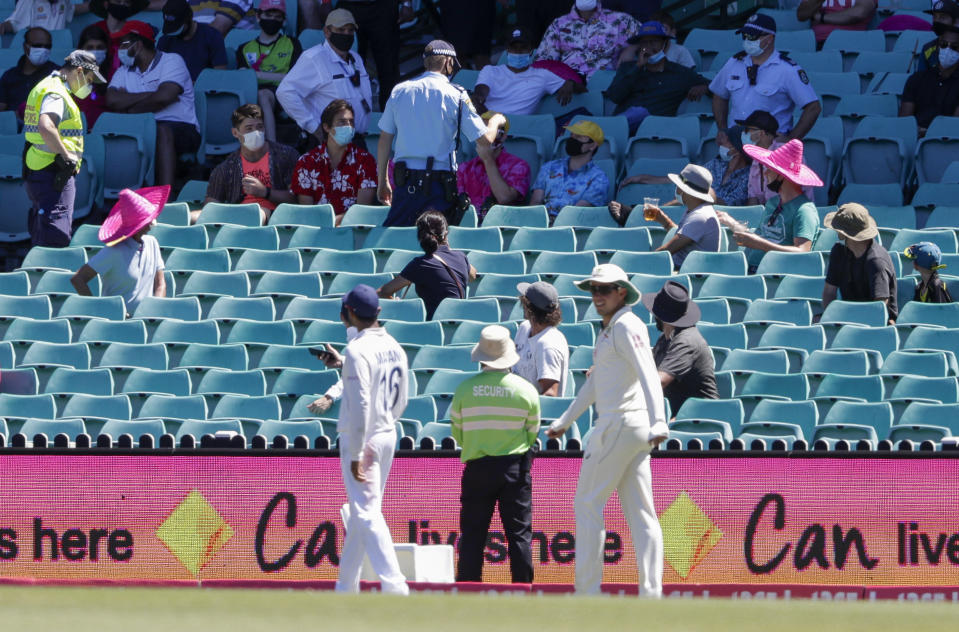 Police, top, remove spectators from the game during play on day four of the third cricket test between India and Australia at the Sydney Cricket Ground, Sydney, Australia, Sunday, Jan. 10, 2021. (AP Photo/Rick Rycroft)