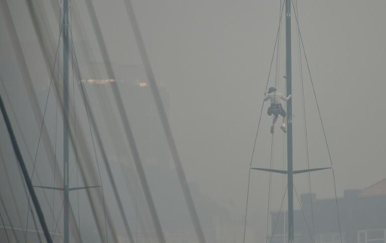 A sailor climbs the mast of a yacht enveloped in haze caused by nearby bushfires at the Cruising Yacht Club of Australia in Sydney on December 10, 2019