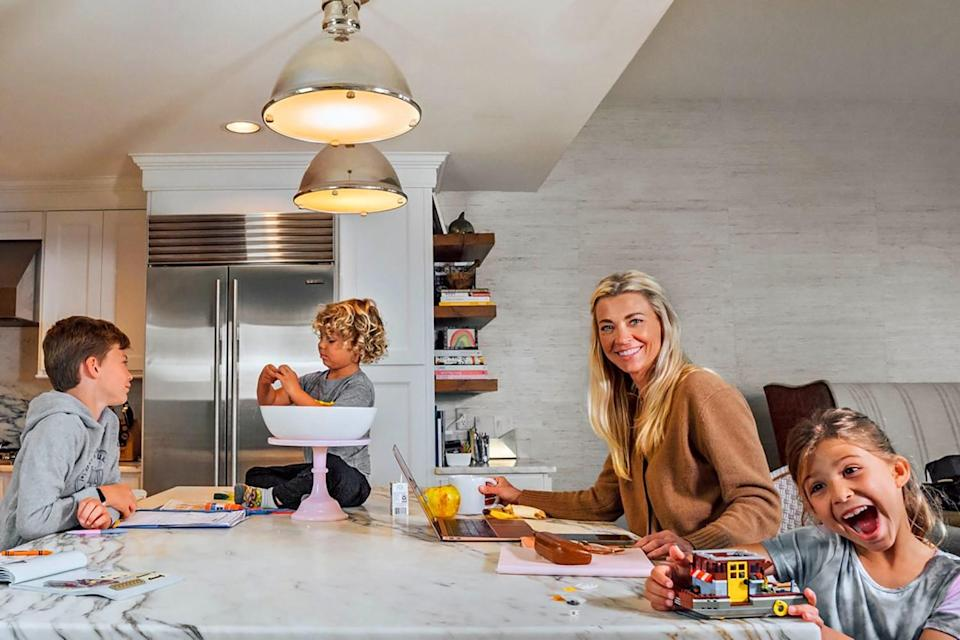 A woman and three children at a kitchen island