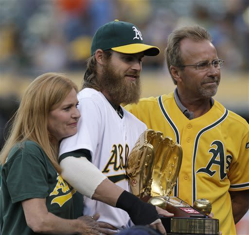 Oakland Athletics' Josh Reddick, center, poses with his mother Cheryl, left, and father Kenny after receiving the AL Golden Glove award before a baseball game against the Detroit Tigers, Friday, April 12, 2013, in Oakland, Calif. (AP Photo/Ben Margot)