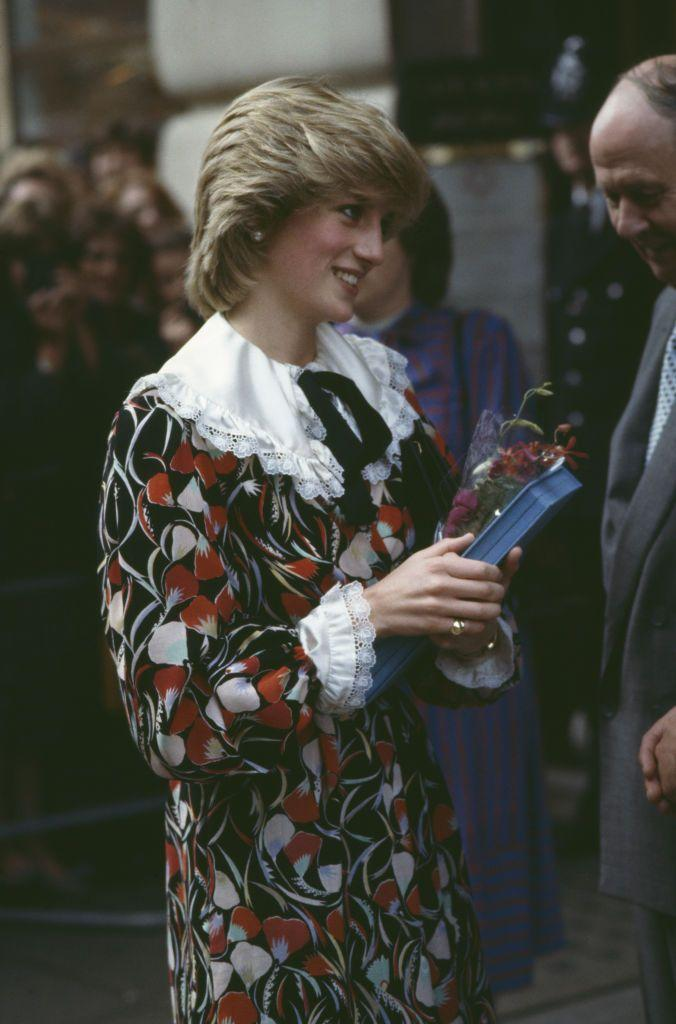 <p>Diana wearing a white, red and black floral dress with a ruffled oversized collar in Brixton, London, November 1983.</p>