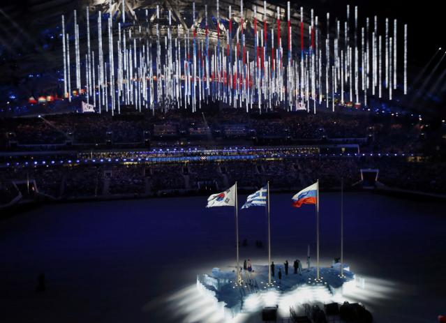 The South Korean, Russian and Greek (L-R) national flags are seen raised during the closing ceremony for the 2014 Sochi Winter Olympics, February 23, 2014. REUTERS/Issei Kato (RUSSIA - Tags: OLYMPICS SPORT)