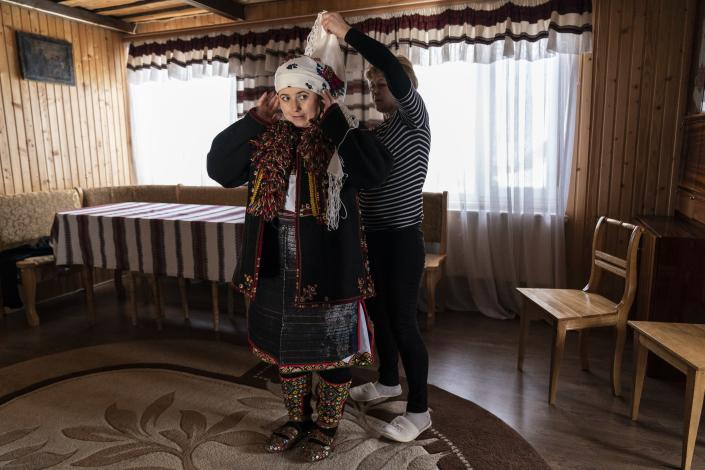 A neighbor helps Dr. Viktoria Mahnych to wear a Hutsul's traditional colorful clothes preparing to attend the Orthodox Christmas celebration in Iltsi village, Ivano-Frankivsk region of Western Ukraine, Thursday, Jan. 7, 2021. Ukraine is struggling to contain the coronavirus pandemic that has inundated its overburdened medical system, as Dr. Viktoria Mahnych goes door to door providing much needed help to patients.(AP Photo/Evgeniy Maloletka)