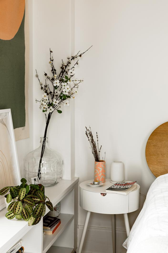 """<div class=""""caption""""> Plants and branches help give off a peaceful aura in the bedroom. </div>"""