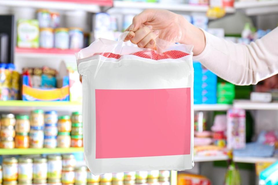 Woman with pack of baby diapers in shop