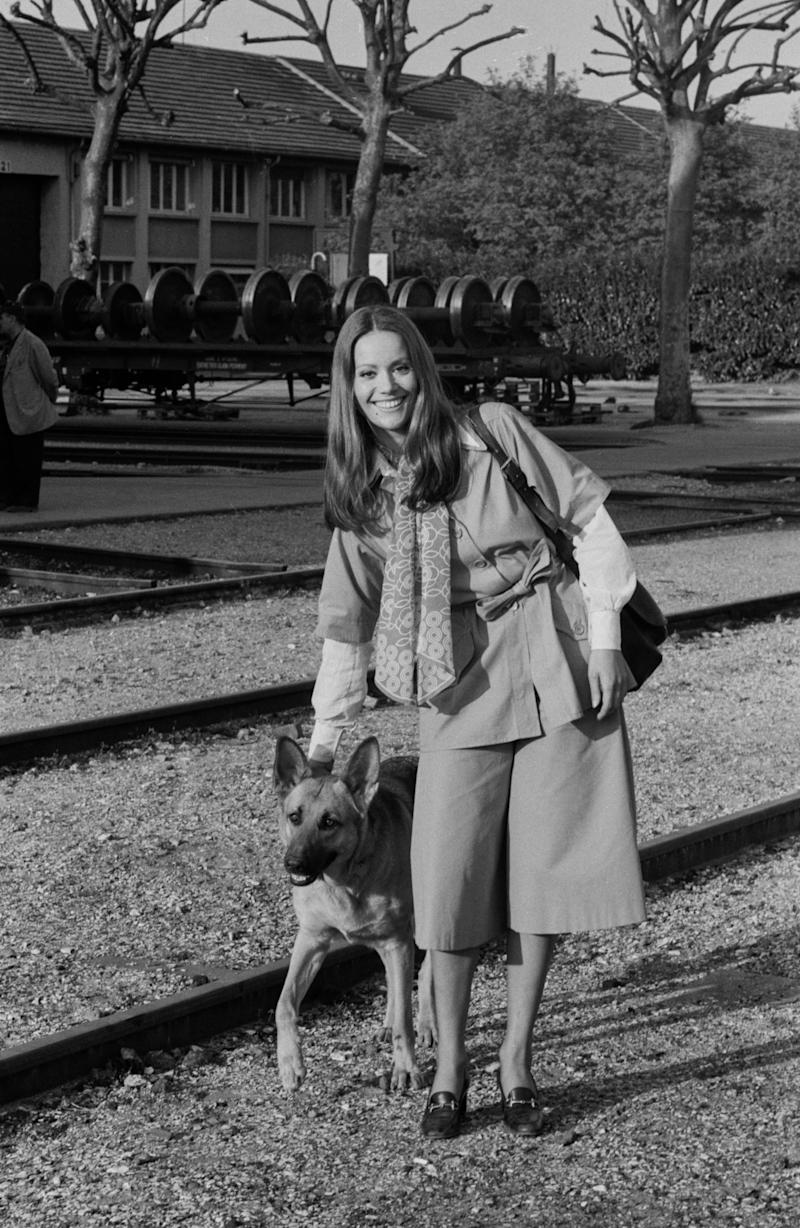Claudine Auger poses with a dog