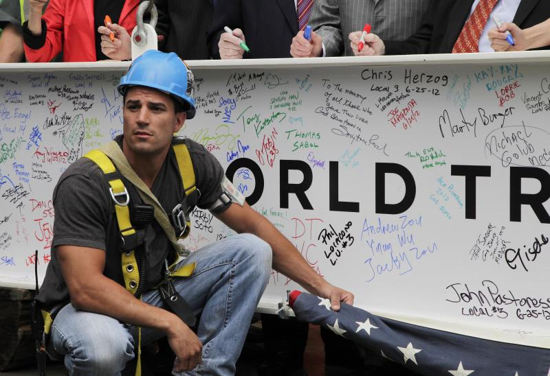 An ironworker holds a furled American flag as officials autograph the ceremonial last beam before it is hoisted to the top of Four World Trade Center, Monday, June 25, 2012. The 72-floor, 977-foot tower is scheduled to open late next year. It's expected to be the first tower completed on the 16-acre site since the 9/11 attacks. (AP Photo/Mark Lennihan)